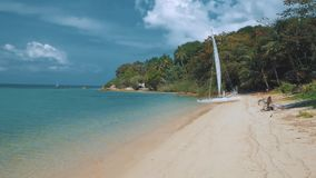 Sail boat, catamaran, on tropical beach with blue water. Steadicam shot stock video footage