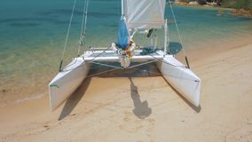 Sail boat, catamaran, on tropical beach with blue water. Steadicam shot stock footage