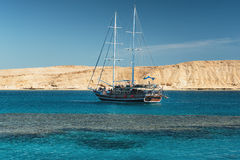 Sail boat in the coral sea near island. Summer vacation Royalty Free Stock Photos
