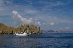 Sail boat cruising the ocean around rocky islands Royalty Free Stock Images