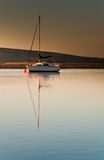Sail boat in dawn light stock photography