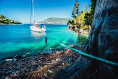 Sail boat docked alone in emerald hidden lagoon among picturesque mediterranean nature Ionian Islands, Greece.  stock photo