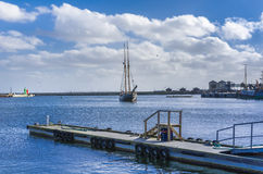 Sail boat entering the harbour Stock Photography