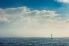 Sail boat in the foggy sea in a calm early morning Royalty Free Stock Photos