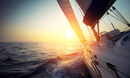 Sail boat. Gliding in open sea at sunset royalty free stock photos