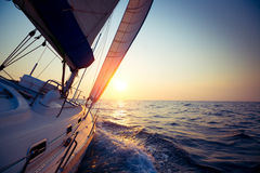 Sail boat. Gliding in open sea at sunset Stock Photos