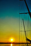 Sail boat gliding in sea at sunset Stock Image