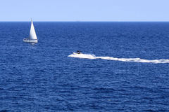 Sail boat and jet boat. Sail boat running against a jet boat Stock Images