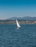 Sail boat on a lake with mountains as background Royalty Free Stock Photography