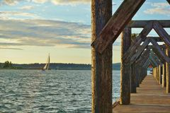 Sail Boat on Lake Passing by Wooden Dock Royalty Free Stock Images
