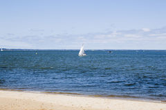 Sail boat in the middle of the sea near the coast Stock Photo