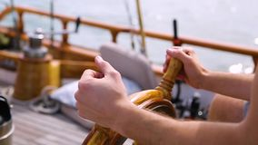 Closeup of a steering wheel and deck of a wooden antique Sail boat navigating in the ocean sunny day showing the wooden parts and. Sail boat navigating in the stock video