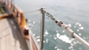 Closeup of the deck of a wooden antique Sail boat navigating in the ocean sunny day showing the wooden parts and. Sail boat navigating in the ocean sunny day stock video footage