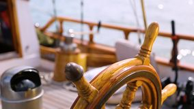 Closeup of a steering wheel and deck of a wooden antique Sail boat navigating in the ocean sunny day showing the wooden parts and. Sail boat navigating in the stock footage