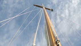 Sail boat navigating in the ocean sunny day showing the wooden parts and Closeup of the sail of a wooden antique. Sail boat navigating in the ocean sunny day stock video footage