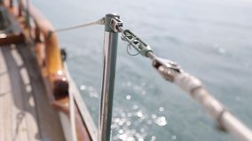 Sail boat navigating in the ocean sunny day showing the wooden parts and Closeup of the deck of a wooden antique. Sail boat navigating in the ocean sunny day stock video footage