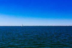 Sail boat over Lake Erie under blue sky, in Cleveland, USA royalty free stock photo