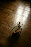 Sail boat in the parquet floor. Retro light royalty free stock photography