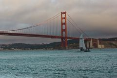 Sail boat passing under the famous Golden Gate Bridge Stock Image