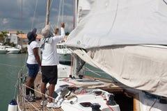 Two men repairing sails. stock images