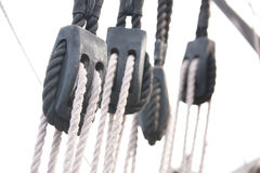 Sail Boat Rigging: Lines and Pulleys. Wooden pulleys and ropes on an old wooden sail boat royalty free stock image