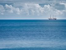 Sail boat sailing on calm blue sea water.  Royalty Free Stock Photography