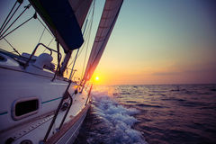 Sail boat. With set up sails gliding in open sea at sunset Royalty Free Stock Photography