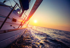 Sail boat. With set up sails gliding in open sea at sunset Royalty Free Stock Photo