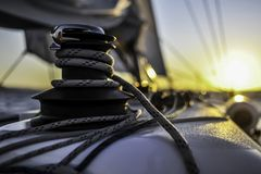Sail boat with set up sails gliding in open sea at sunset royalty free stock photography