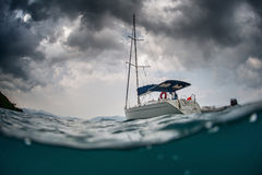 Sail boat. Split shot of anchored sail boat with heavy clouds in sky Stock Photos