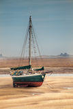 Sail boat stranded at low tide on sand Stock Photo