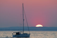 Sail boat and sunset on the horizon above sea Royalty Free Stock Image