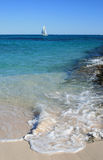 Sail Boat in Tropical Water. A White Sailing Boat goes passed the tropical Ningaloo Reef, Coral Bay, Western Australia A wave breaks in the foreground stock photos