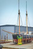 Sail boat with workers in a boatyard being repaired Royalty Free Stock Images