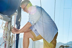 Sail boat  yacht mooring. Portrait of senior man tying knot and securing a mooring for his hobby yacht sail boat Royalty Free Stock Image