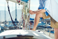Sail boat yacht mooring. Portrait of senior man tying knot and securing a mooring for his hobby yacht sail boat stock image