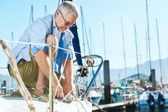 Sail boat yacht mooring. Portrait of senior man tying knot and securing a mooring for his hobby yacht sail boat stock images