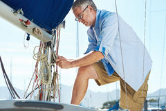 Sail boat yacht mooring. Portrait of senior man tying knot and securing a mooring for his hobby yacht sail boat royalty free stock photography