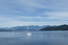 White sail boats anchored in peaceful blue waters Stock Photo