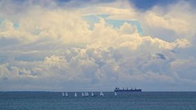 Sail boats, a freighter and a storm Stock Photos