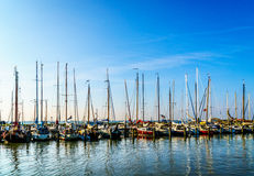 Sail boats moored in the small harbor of the historic fishing village of Marken. In the Netherlands under clear skies Royalty Free Stock Photography