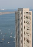 Sail boats parked outside tall building. A tall modern building next to the Boston Harbor with sail boats Stock Images