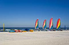 Sail boats, pedal boats and kayaks. A series of colorful pedal boats, kayaks and catamaran sail boats at a resort. Blue sky and turquoise sea. Plenty of space Stock Images