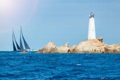 Sail boats in Sardinia, Monaci island lighthouse Stock Image