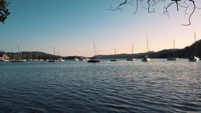 Sail boats sit on a calm Lake Windermere during sunset in Cumbria, UK. Sailing boats at Lake Windermere in Spring 2019 stock video footage