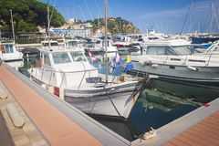 Sail Boats and yachts parked at docks of Blanes, Costa Brava, Spain. Sea port with white yachts on summer clear day. Sail Boats and yachts parked at docks of royalty free stock photos