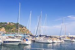 Sail Boats and yachts parked at docks of Blanes, Costa Brava, Spain. Sea port with white yachts on summer clear day. Sailboat harbor, many beautiful moored stock photo