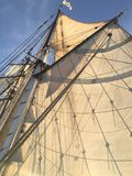 Sail and mast of a traditional ship on a sunny day with blue sky stock images