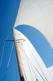 Sail and mast on yacht, view from deck of boat. Sail and mast on yacht on sunny day, view from deck of boat Royalty Free Stock Photos