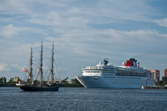 Sail ship and a cruise ship. Danish fullrigger Georg Stage entering and cruise ship Zenith leaving harbor of Saint Petersburg in Russia in a sunny summer day Royalty Free Stock Images